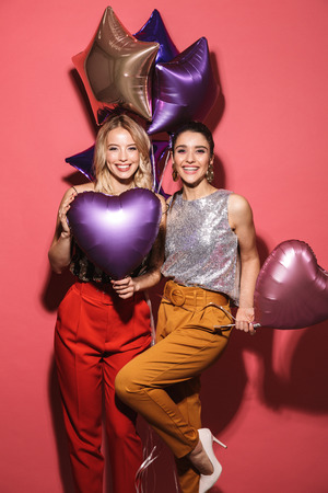 Image of two fancy girls 20s in stylish outfit laughing and holding festive balloons isolated over red background Stock Photo