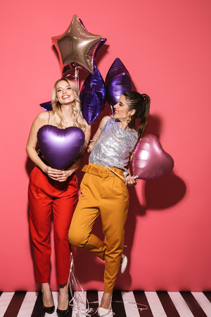 Image of two glamour girls 20s in stylish outfit laughing and holding festive balloons isolated over red background Stock Photo