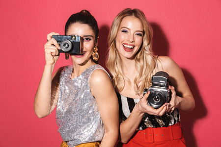 Image of two adorable girls 20s in stylish outfit holding and photographing on retro camera isolated over red background