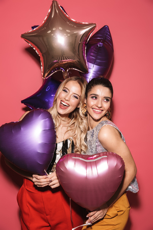 Image of two gorgeous girls 20s in stylish outfit laughing and holding festive balloons isolated over red background Stock Photo