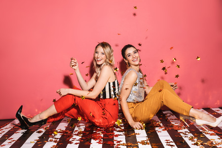 Portrait of two modern women 20s in stylish outfit celebrating and sitting on floor with falling confetti isolated over red background
