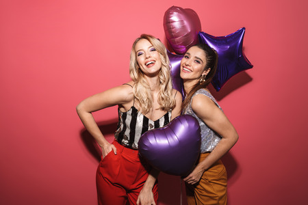 Image of two joyous girls 20s in stylish outfit laughing and holding festive balloons isolated over red background