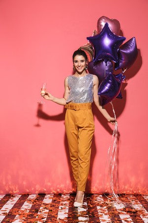 Portrait of brunette woman 20s in stylish outfit holding festive balloons and drinking champagne on party isolated over red background Imagens