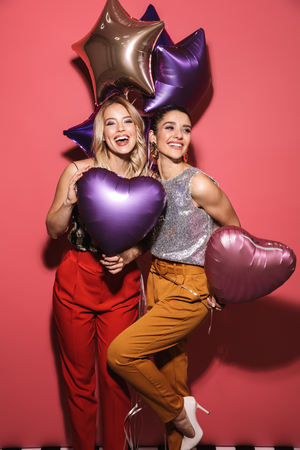 Image of two caucasian girls 20s in stylish outfit laughing and holding festive balloons isolated over red background Stock Photo
