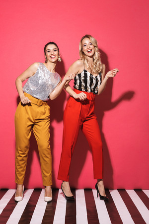 Full length photo of two beautiful women 20s in trendy outfit smiling and having fun isolated over red background Stock Photo