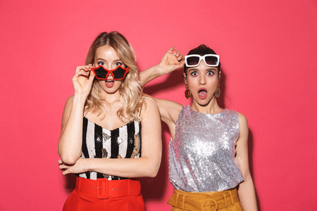 Photo of two surprised women 20s in trendy outfit and sunglasses smiling at camera isolated over red background
