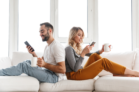 Image of young cute loving couple indoors at home using mobile phones.