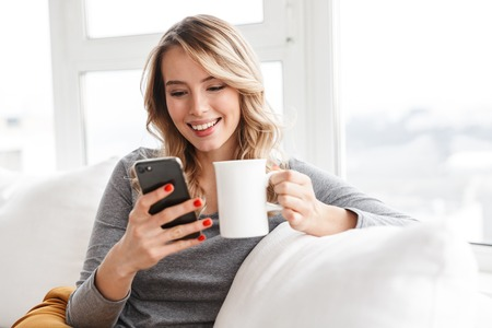 Image of cute pretty woman sitting indoors at home holding cup drinking tea using mobile phone. Archivio Fotografico