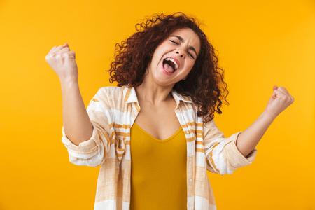 Image d'une femme heureuse de 20 ans aux cheveux bouclés criant et se réjouissant, isolée sur fond jaune