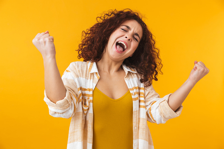 Image of happy woman 20s with curly hair screaming and rejoicing, isolated over yellow background