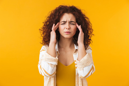Image of tense woman 20s with curly hair rubbing her temples because of headache, isolated over yellow background Imagens - 119995843