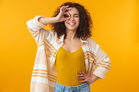 Image of a beautiful young curly girl posing isolated over yellow wall background with okay gesture. Archivio Fotografico