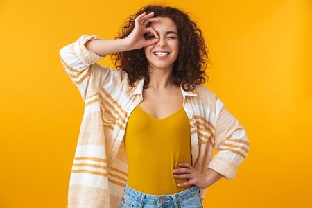 Imagen de una hermosa joven rizada posando aislada sobre fondo de pared amarilla con gesto bien.