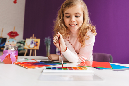 Lovely little girl painting a picture at the table at home