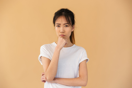 Portrait of obused asian woman wearing basic t-shirt posing at camera with angry look isolated over beige background in studio