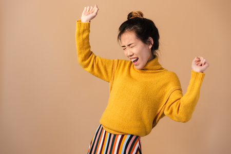 Photo of attractive japanese woman wearing sweater smiling and dancing isolated over beige background in studio