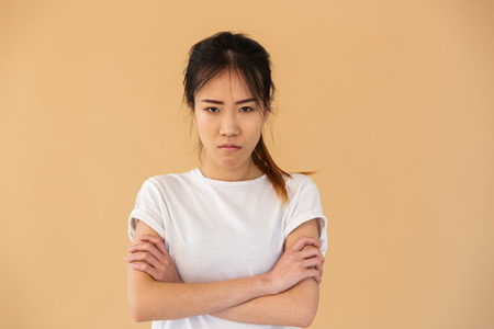 Portrait of outraged asian woman wearing basic t-shirt posing at camera with angry look isolated over beige background in studio Stock Photo