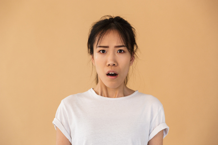 Portrait of confused asian woman wearing basic t-shirt wondering and looking at camera with open mouth isolated over beige background in studio 스톡 콘텐츠