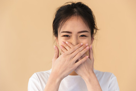 Image of joyous chinese woman wearing basic t-shirt covering her mouth with hands isolated over beige background in studio Banco de Imagens