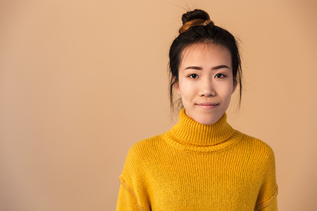Image of young japanese woman wearing sweater smiling and looking at camera Stock Photo
