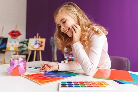 Jolie petite fille peignant une image à la table à la maison Banque d'images