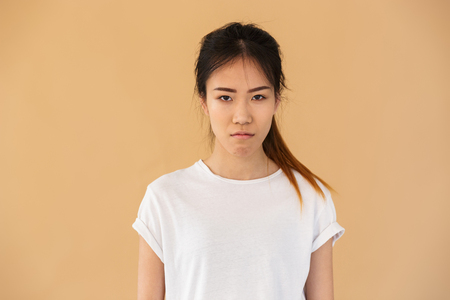 Portrait of offended asian woman wearing basic t-shirt posing at camera with angry look isolated over beige background in studio