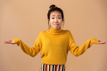 Afbeelding van een onschuldige Japanse vrouw die een trui draagt en handen overgeeft met verbazing geïsoleerd over een beige achtergrond in de studio