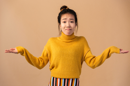 Image of innocent japanese woman wearing sweater throwing up hands with puzzlement isolated over beige background in studio Foto de archivo