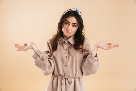 Image of a beautiful confused young woman posing isolated over beige wall background.