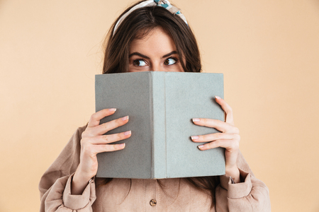 Image of beautiful young pretty woman posing isolated over beige background wall holding book reading.