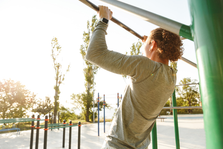 Confident young sportsman doing exercices at the horizontal bar outdoors
