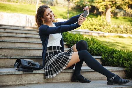 Joyeuse jeune écolière assise à l'extérieur sur un escalier, utilisant un téléphone portable, prenant un selfie