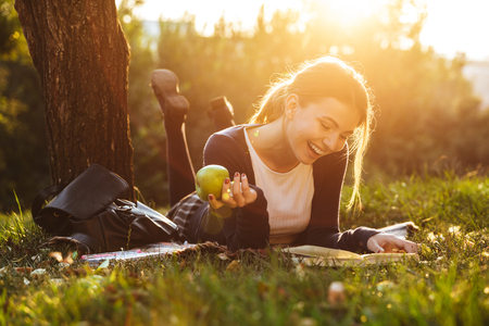 Cheerful teenage girl wearing uniform studying while relaxing at the park on a blanket Banque d'images