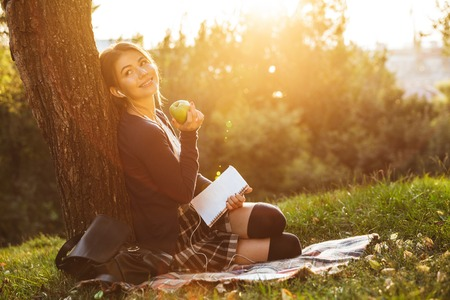 Cheerful teenage girl wearing uniform studying while relaxing at the park on a blanket