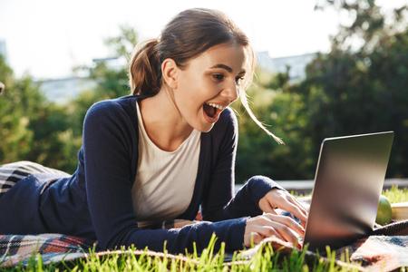 Bastante adolescente recostado sobre un césped en el parque, estudiando, usando la computadora portátil