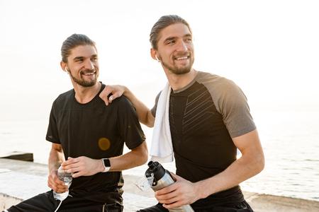Twee tweelingbroers die samen oefeningen doen op het strand
