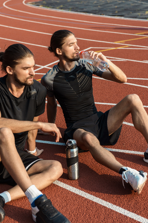 Two twin brothers resting after workout while sitting on a stadium, drinking warer