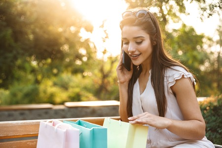 Portrait of a beautiful young woman wearing dress sitting on a bench outdoors, carrying shopping bags, holding mobile phone