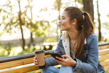 Lächelnde junge Frau mit Jacke sitzt auf einer Bank im Park, benutzt Handy, trinkt Kaffee zum Mitnehmen