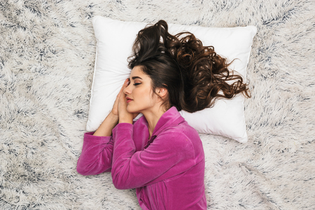 Photo from above of brunette woman 20s with long curly hair wearing girlish housecoat lying and sleeping on white fur in apartment