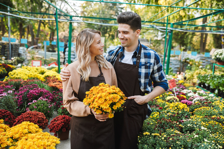 Photo of emotional happy young two colleagues gardeners at the workspace over plants holding flower plant. Stock Photo