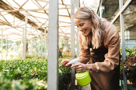 Image of a happy young woman gardener at the workspace over plants.