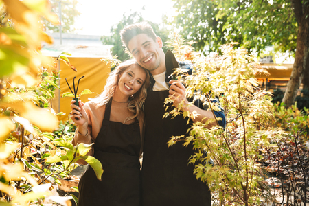 Image of a happy young two colleagues gardeners at the workspace over plants.