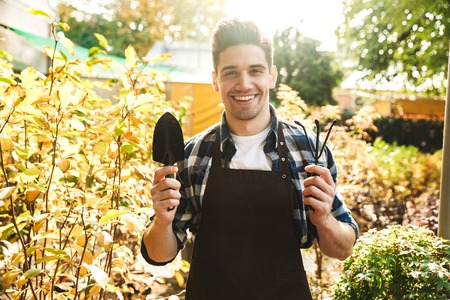 Image of a happy young man gardener at the workspace over plants. Stock Photo