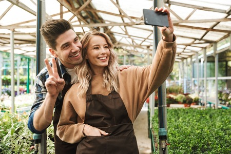 Image of a happy young loving couple gardeners at the workspace over plants take a selfie by mobile phone.