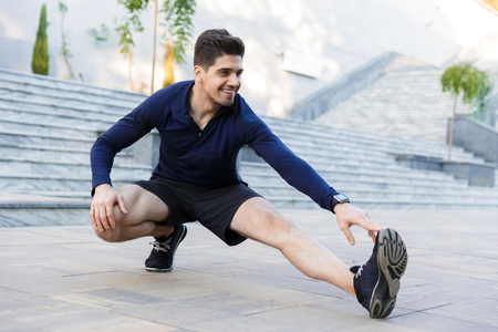 Confident young sportsman doing stretching exercises outdoors Stock Photo