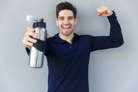 Confident smiling sportsman holding water bottle while standing isolated over gray background
