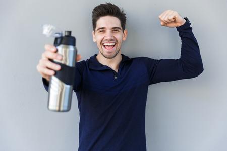 Sportif souriant confiant tenant une bouteille d'eau en se tenant isolé sur fond gris Banque d'images