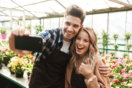 Photo of emotional happy young two colleagues gardeners at the workspace over plants take a selfie by mobile phone showing thumbs up. Stock Photo