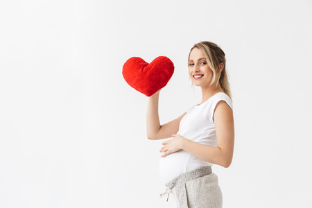 Beautiful young pregnant woman standing isolated over white background, holding heart